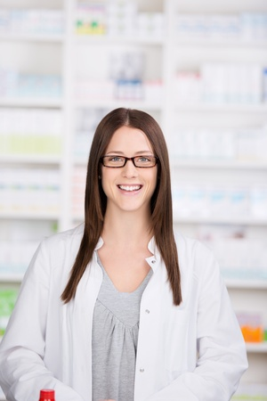 dispense: Smiling pharmacist in a pharmacy standing behind the counter waiting to serve patients and dispense medicines