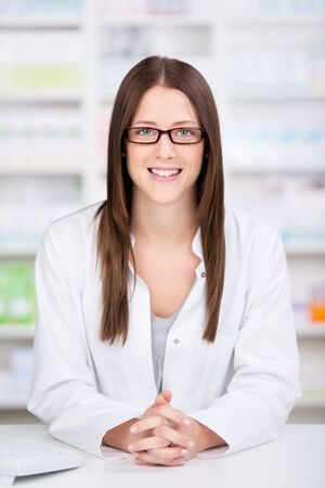 dispense: Friendly young female assistant or pharmacist standing behind the counter in the pharmacy ready to dispense medicine Stock Photo