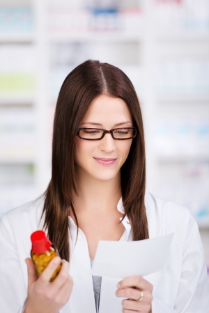 dispensing: Attractive young female pharmacist dispensing medication standing with a bottle of pills in one hand a a receipt in the other, blurred shelving in the background