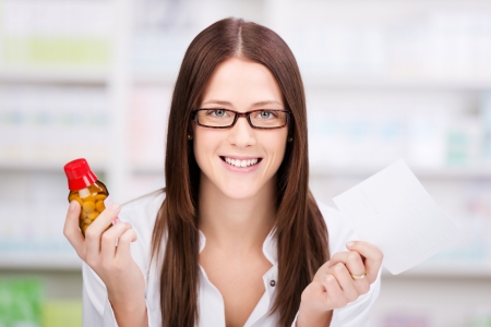 Attractive young female pharmacist holding a prescription and the bottle of medication in her hands photo