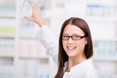A cheerful young woman pharmacist with a bottle of medicine standing in pharmacy drugstore photo