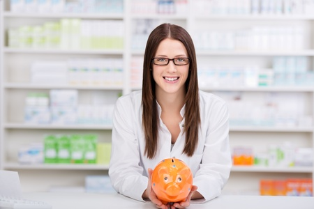 Smiling pharmacist with glasses showing piggybank for a savings concept photo
