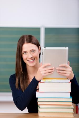 classroom teacher: Donna sorridente in possesso di un tocco ipad sulla cima di libri