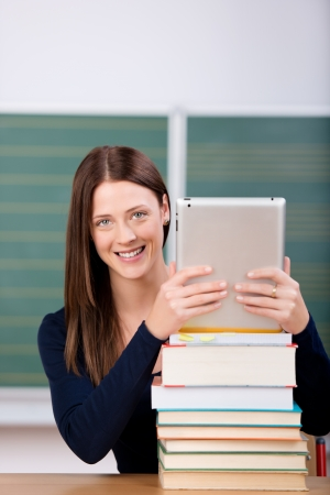 pile of books: Smiling woman holding an touchpad on top of books