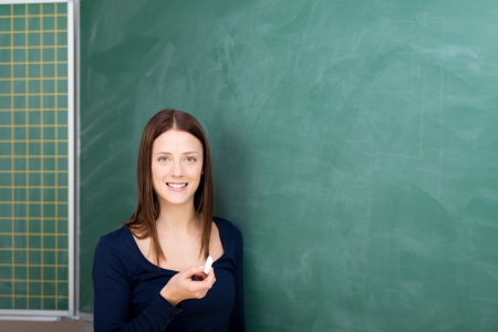 Smiling student holding a chalkboard in front of blackboard photo