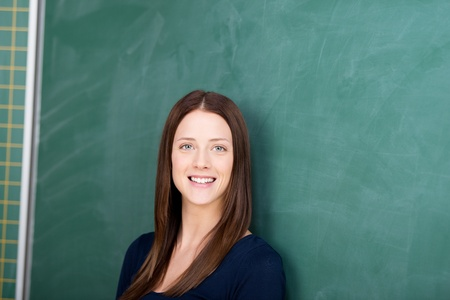 Smiling female student standing in front of blackboard Stock Photo - 21341189