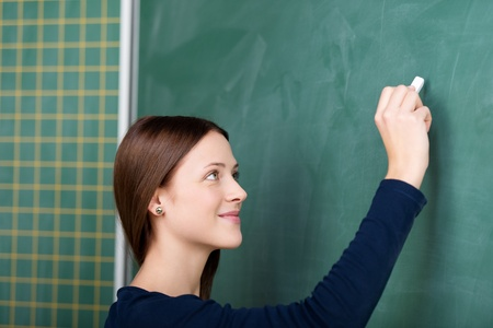 Smiling student writing on blackboard in a close up portrait Stock Photo - 21341191