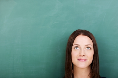 portrait of young woman standing against blackboard photo