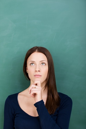young thoughtful beautiful woman standing against blackboard Stock Photo - 21341199