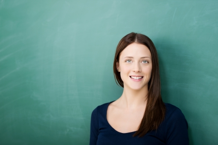 portrait of happy woman standing against blackboard Stock Photo - 21341201