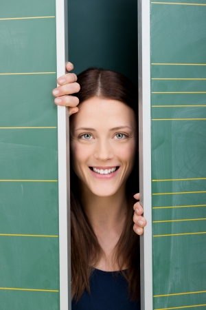 Image of a beautiful young female student smiling and peeping out from behind two panels. photo
