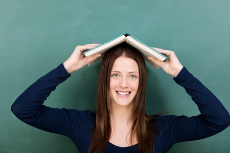 fair skin: Photograph of a pretty young female student carrying an open book on her head and giving a cute smiling.