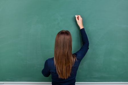 writing black: Woman with long brunette hair standing with her back to the camera writing on a clean blank green blackboard