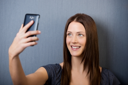Image of a beautiful young female clicking picture of herself by some cellphone. photo