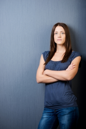 A standing portrait of a beautiful young female with her arms folded and looking straight. photo