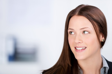 near side: Close-up picture of an attractive young business woman looking away and smiling in an office setting.