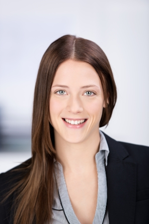 retrato: Retrato de perfil de una encantadora mujer de negocios joven que es feliz y sonriente en un entorno de oficina.