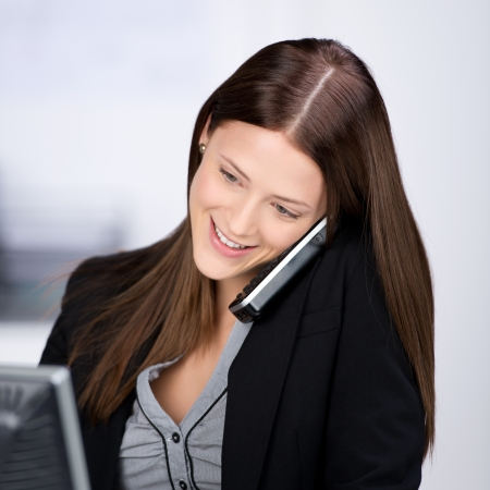 Smiling businesswoman calling through telephone at the office photo