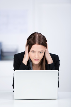 Portrait of serious businesswoman reading something on her laptop photo