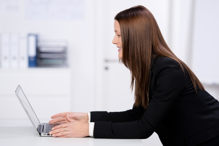 Smiling businesswoman working at her laptop in a side view shot photo