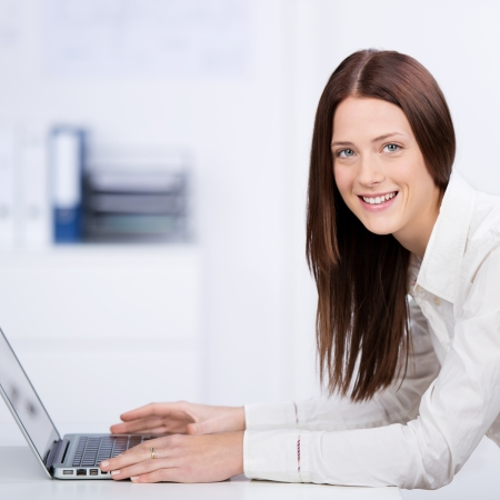 Pretty businesswoman smiling and typing through her laptop Stock Photo - 21341238