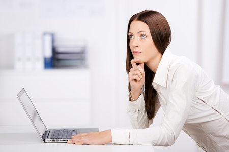 Businesswoman thinking and holding her chin in front of laptop photo