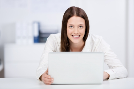 Smiling businesswoman sitting and working at her laptop inside the office photo