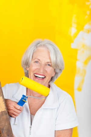Portrait of happy senior woman holding roller against yellow painted wall photo