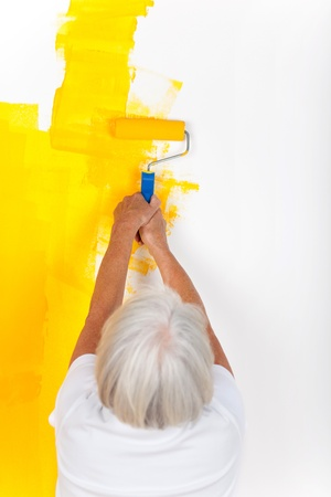 Woman is painting with a roller in yellow color photo