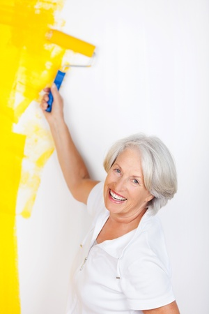Portrait of happy senior woman painting wall with paint roller photo
