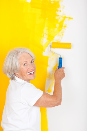 Active senior woman painting a wall in her house a vibrant yellow with a paint roller turning to smile happily at the camera photo