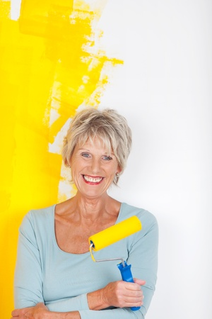 Mature woman keeping busy, while painting her walls photo