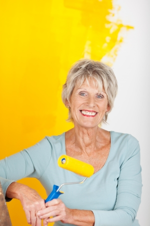 Mature woman is painting a wall in yellow photo