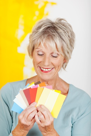 deciding: Happy senior woman choosing color from swatches against half painted wall