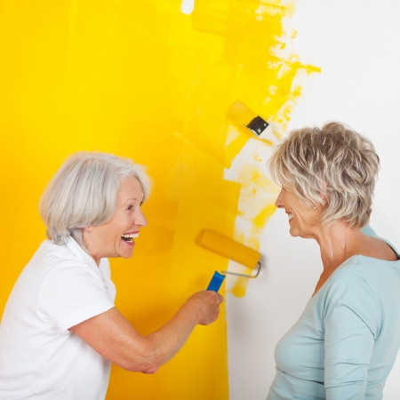Side view of happy senior women painting wall with yellow paint photo