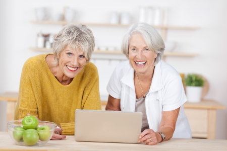 Portrait of happy senior female friends with laptop leaning on kitchen counter photo