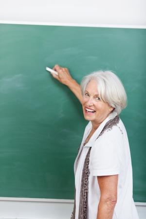 college professor: Happy senior teacher writing on chalkboard in class