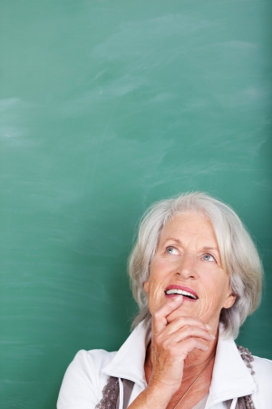 reverie: Senior woman standing thinking against a green blackboard with blank copyspace, head and shoulders portrait