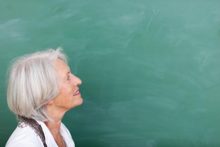 Education in old age - an elderly woman continuing her education in old age stands looking at a blank green blackboard, head and shoulders portrait photo