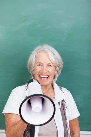 Laughing beautiful vivacious senior woman with a megaphone in her hand standing in front of a green blackboard photo