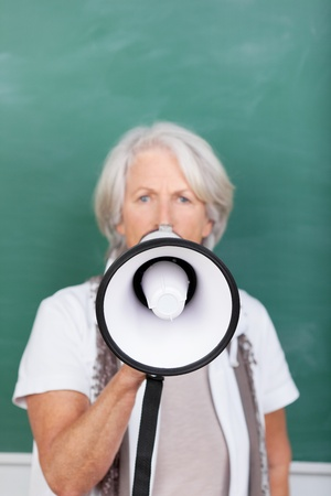 Portrait of angry senior teacher speaking into megaphone against chalkboard photo