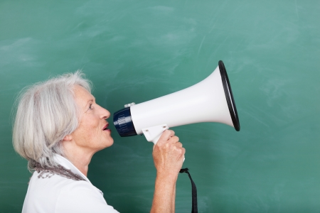protestor: Senior woman with a megaphone standing sideways in front of a blackboard with it raised to her lips