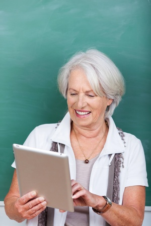 Happy female teacher using digital tablet against chalkboard in class Stock Photo - 21341268
