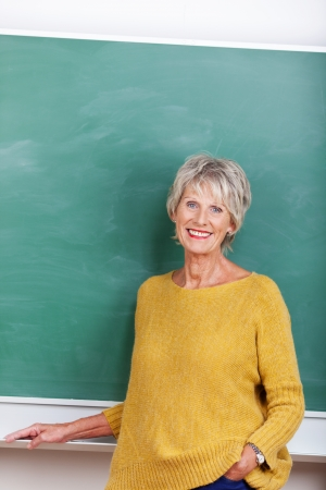 Attractive mature teacher standing in front of a blackboard photo