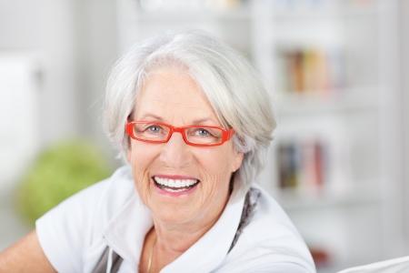 Mujer mayor de moda en gafas modernas con marcos de color rojo anaranjado que sonríe feliz mientras mira a la cámara