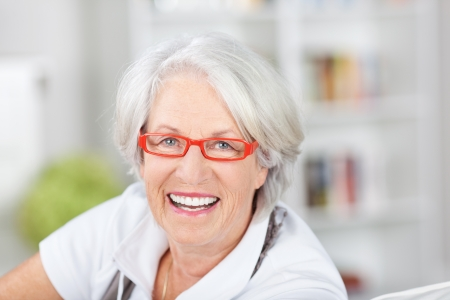 Trendy senior woman in modern glasses with orange red frames smiling happily as she looks at the camera photo