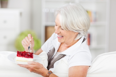 unhealthful: Happy senior woman having pastry while sitting on sofa Stock Photo