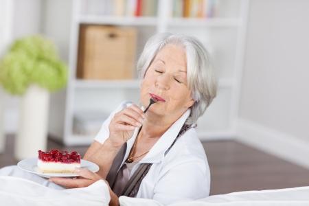 extase: Senior vrouw genieten van een fruitige crème taart op een sofa zitten likken de lepel met haar ogen in extase gesloten