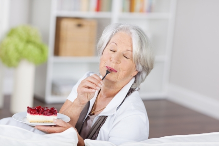 Senior woman enjoying a fruity cream cake sitting on a sofa licking the spoon with her eyes closed in ecstasy photo