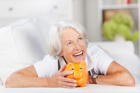 Smiling senior woman lying relaxing on a sofa with a piggy bank in front of her laughing as she imagines all the things she can do with her nest egg photo